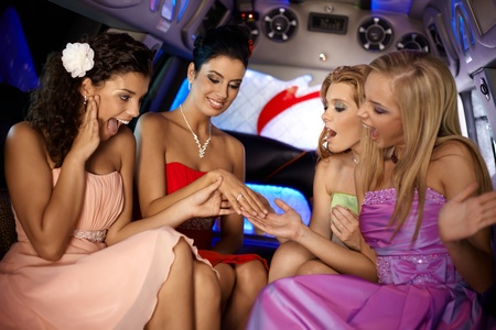 Hen party in limousine, girls looking at her friends engagement ring. photo