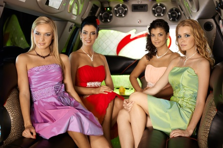 four person: Beautiful elegant women sitting in limousine, looking at camera.