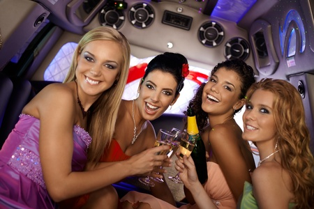 have on: Pretty girls celebrating in limousine, clinking glasses, smiling. Stock Photo