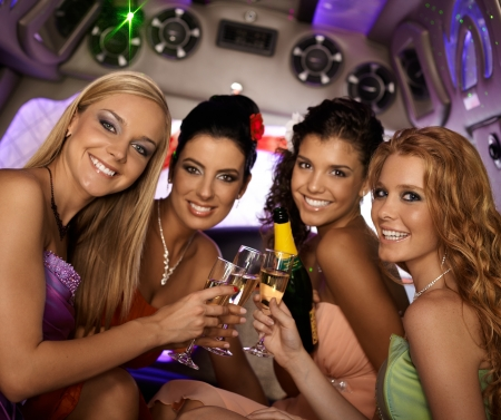 hen party: Happy women celebrating in limousine, smiling, looking at camera. Stock Photo