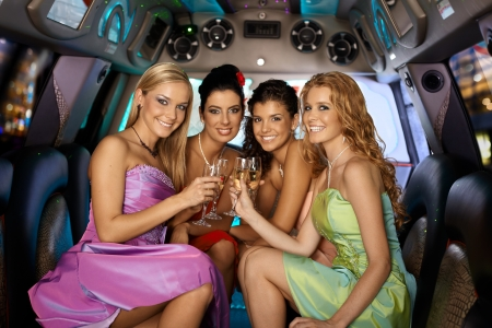 hen party: Group of beautiful elegant smiling girls celebrating in limousine.
