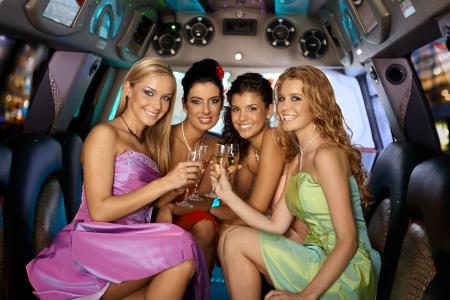 despedida de soltera: Grupo de bellas chicas elegantes sonrientes celebrando en limusina.