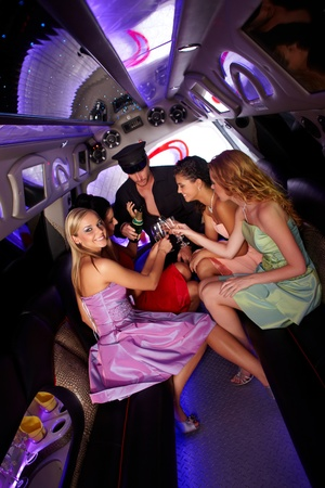 Party time in limousine with elegant young girls and chauffeur, drinking champagne. photo