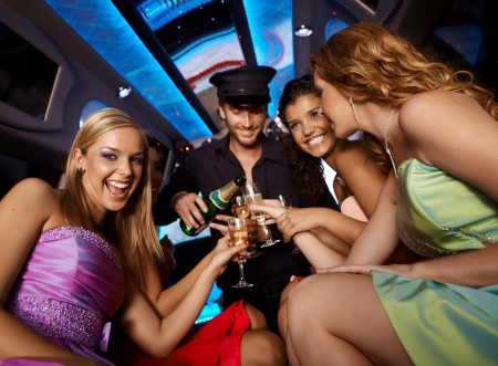 Happy girls having fun in limo, drinking champagne. photo