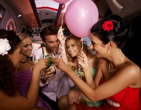 clinking: Party fun with champagne in limousine.