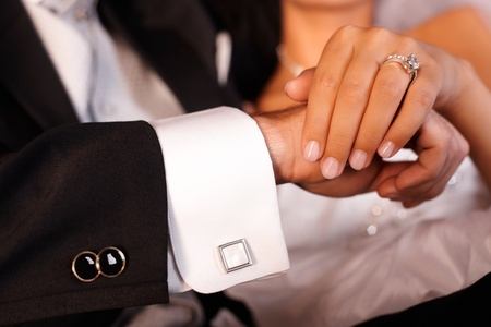 cuff: Closeup photo of bride and groom hands with engagement ring. Stock Photo