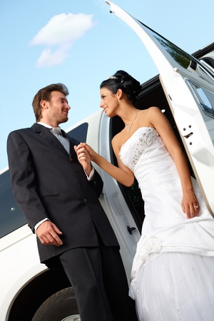 Bride and groom on wedding-day getting out of limousine. photo