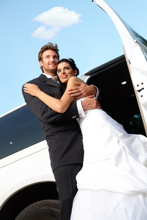 outdoor photo: Happy married couple embracing on wedding-day.