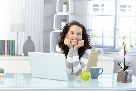 workroom: Portrait of happy young woman sitting in bright study, laptop computer, mug, green apple on desk.