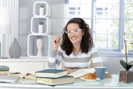 having breakfast: Young woman studying in morning at home for college, breakfast and textbook. Stock Photo
