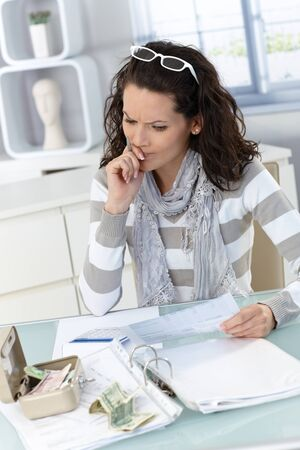 hair problem: Troubled woman calculating budget at home, money, bills and finances. Stock Photo
