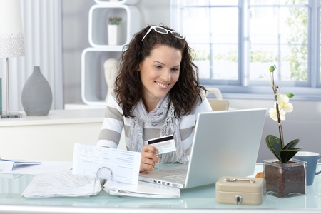 room card: Smiling woman paying online for purchase with creditcard, using laptop computer.