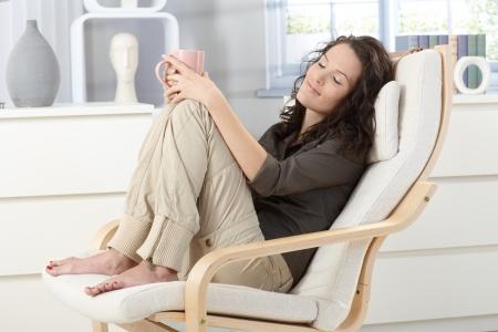 closed eyes: Vrouw ontspannen met gesloten ogen en een kopje thee in leunstoel thuis, dagdromen.