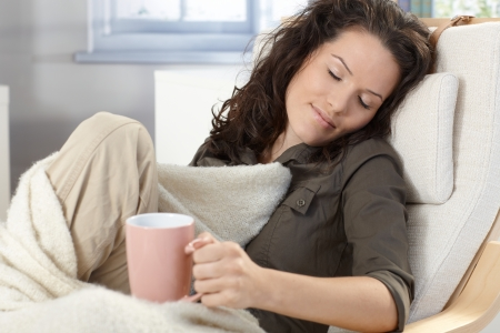 wrapped up: Young woman relaxing in armchair under blanket at home, holding tea mug, smiling, daydreaming. Stock Photo
