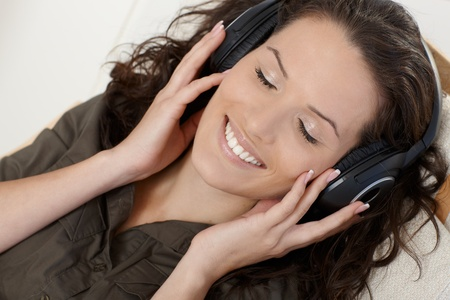 Closeup portrait of happy woman enjoying music with eyes closed via headphones. photo