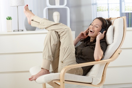 Woman having fun , listening to music with headphones, singing in armchair at home. photo