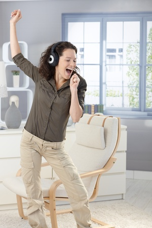 enjoy space: Happy woman singing and dancing with headphones at home, having fun. Stock Photo