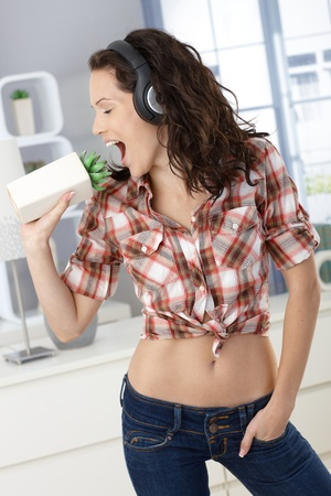 Pretty woman enjoying singing at home, as fun using plant as microphone, listening to music via headphones. photo