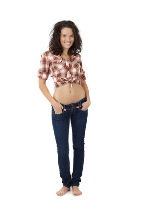 Pretty woman in trendy sexy jeans and shirt posing with bare belly, smiling, isolated on white. photo