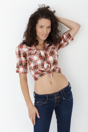 checked shirt: Portrait of beauty posing sexy in trendy jeans and shirt, nude belly, isolated on white. Stock Photo