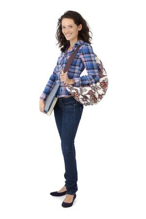 Happy pretty university student girl with handbag and books, smiling. photo