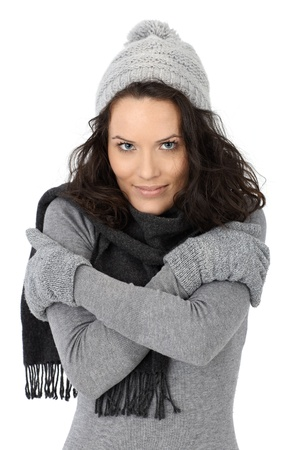 feeling good: Beautiful woman feeling cold in winter, wearing scarf cap and gloves, isolated on white.