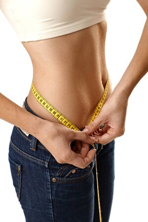 Slim female body measuring belly size with tape measure. photo
