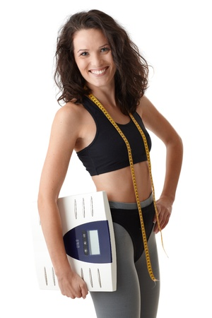 Happy sporty woman posing in sportswear with scale and tape measure. Stock Photo - 12174535