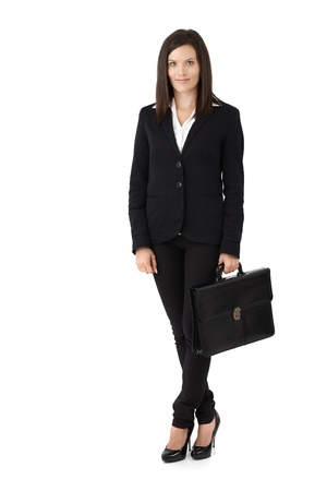 Young smart businesswoman posing with briefcase, smiling confidently, cutout on white. photo