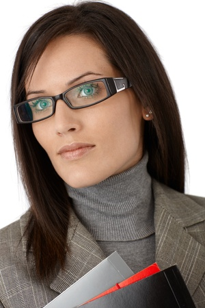unsmiling: Closeup portrait of determined young businesswoman in glasses.