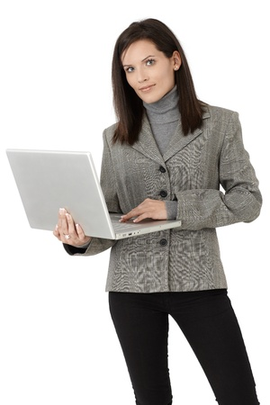 formal attire: Businesswoman portrait, standing with laptop computer, smiling at camera confidently.