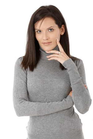 Confident beauty posing in grey high-neck sweater, smiling at camera. Stock Photo - 12174655