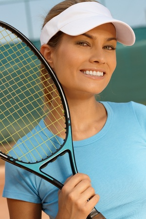 Portrait of pretty female tennis player, smiling, looking at camera. photo