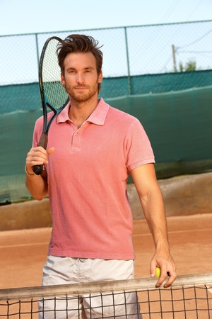 tennis racket: Handsome tennis player standing on hard court holding tennis racket.