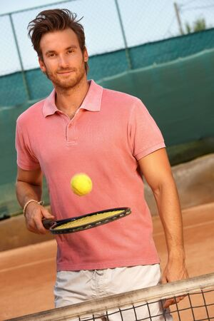 Handsome young man playing tennis on hard court, smiling, looking at camera. photo