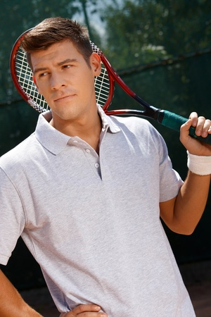 offish: Portrait of young male tennis player holding tennis racket, looking away. Stock Photo