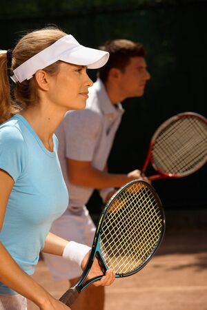 Young people playing tennis, mixed doubles, side view. photo