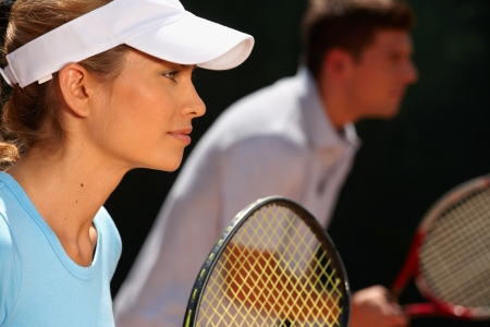 jugando tenis: La mujer joven y un hombre jugando dobles mixtos juego de tenis, vista lateral.