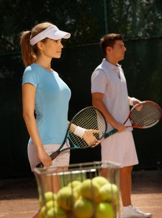 jugando tenis: Los jóvenes jugadores de tenis jugando dobles mixtos en la cancha de tenis. Foto de archivo