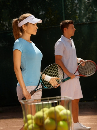 Young tennis players playing mixed doubles on tennis court. photo