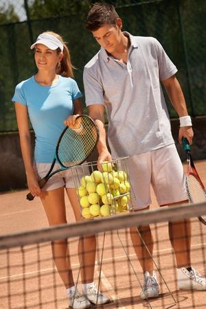 jugando tenis: Atractivo joven pareja jugando al tenis en canchas duras. Foto de archivo