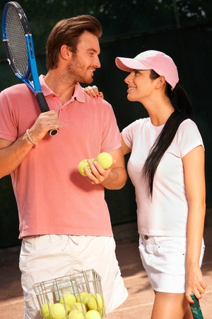 each: Loving couple standing on tennis court, smiling, looking at each other.