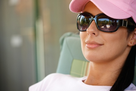 Pretty woman relaxing, wearing sunglasses, smiling. photo