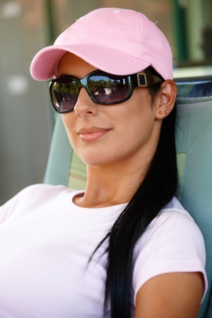 Portrait of attractive smiling woman in baseball cap and sunglasses.