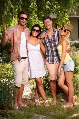 amigos abrazandose: Felices los jóvenes de pie en el verde en verano, que abarca. Foto de archivo
