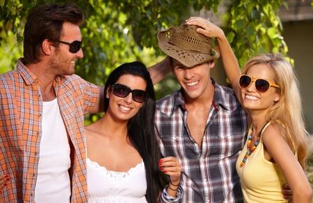 amigos abrazandose: El compañerismo alegre abrazando al aire libre en verano.