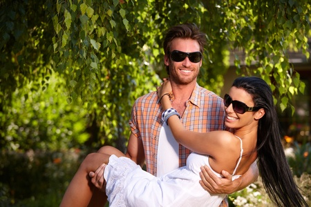 Romantic young couple smiling in the garden, man holding girl in arms. photo