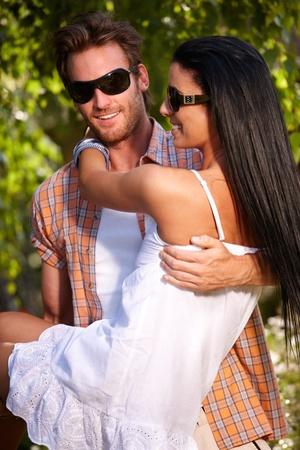 couple enlac�: Bonne jeune couple embrassant dans le jardin � l'�t�, souriant.