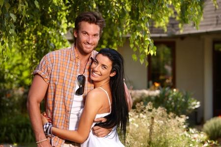 parejas enamoradas: Atractiva pareja de enamorados sonriendo feliz en el verano en el jard�n.