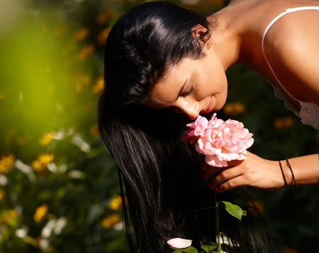 Young woman smelling flower in the garden at summertime. Stock Photo